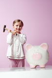 To breake piggy bank. Little girl wants to break piggy bank Stock Image