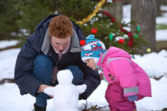 To build a snowman. Mom with daughter and snowman