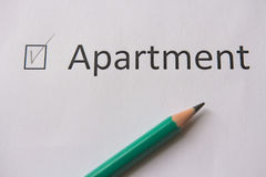 To buy an apartment. word APARTMENT is written on white paper with tick and  gray pencil. Royalty Free Stock Photography