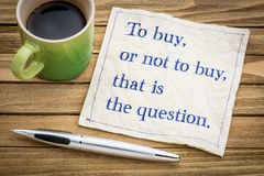 To buy ,or not question. To buy, or not, that is the question. SHpping and decsion copncept. Handwriting on a napkin with a cup of coffee Royalty Free Stock Images