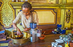 To clean the coffee beans. KIEV, UKRAINE - JUNE 4, 2017: Ethiopian Tigrayan woman washes green coffee beans for the ethnic coffee ceremony, on June 4 in Kiev Royalty Free Stock Photography
