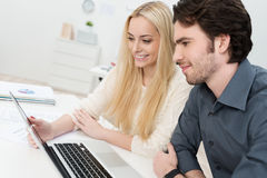 To co-workers in the office working on a laptop. Computer with a beautiful young women smiling as she presents something to her male colleague Royalty Free Stock Images
