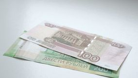 To count money. Hands recount banknotes on a white table. People hand lays out russian rubles banknotes nominals 200 and. 100 on a white background stock video