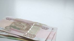 To count money. Money falls on a white table. People hand quickly throws russian rubles banknotes nominals 200 and 100. And coins nominal 10 on a white stock video footage