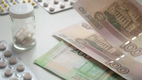 To count money. Pay for medicament drugs. People Buying drugs. Medicine pills or capsules with money on white background. A person pays with Russian rubles for stock video footage