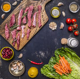 To cut thin slices beef with garlic on a cutting board with a knife for meat, butter and salt, lettuce  wooden rustic background Royalty Free Stock Image