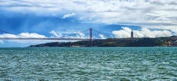 25to de April Bridge a través del río Tagus y de la vista de la ciudad y de la estatua de Jesus Christ, Portugal de Almada Imagen de archivo libre de regalías