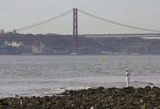 25to del puente de abril visto de la playa de piedra Foto de archivo