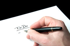 To Do List. A male hand writing a to do list onto white paper Stock Images