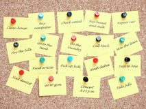 To-do list. Yellow post-it notes with various written to-do tasks affixed to the corkboard royalty free stock images