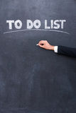 To do list. Close-up of human hand writing to do list on the blackboard Stock Photography