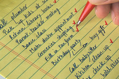 To do list. Close-up of a man's hand with a red pen keeping track of accomplished home tasks to do Stock Photos