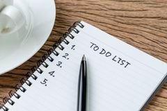 To Do List concept, pen on white paper note pad with handwritten. Headline as To Do List and numbers listed with coffee cup on wood table, writing business stock photos