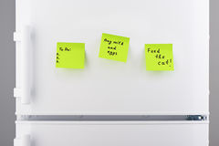 To do list, feed the cat, buy milk and eggs note on refrigerator Royalty Free Stock Photo