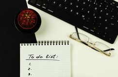 To do list and goals. `to do list` is written on notepad with pen on office table, keyboard , glasses and cactus on white and black background. Top View Royalty Free Stock Photo