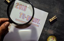 2019 To - Do List handwritten text on the paper with marker, compass and use magnifying glass. On blackboard background. Inspiration, education and celebration stock image