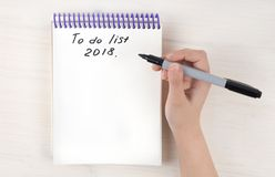 A to-do list in a notepad on spirals. Place for text. A girl`s hand holds a marker. Mock ap royalty free stock image