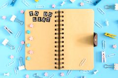 To do list. Notepad on springs with an inscription on the open page. The stationery is in disarray. Blue background. To do list. Notepad on springs with an royalty free stock photos