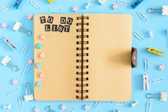 To-do list. Open the notepad on springs with brownish pages. Office supplies are scattered in disorder . Pink and blue. To-do list. Open the notepad on springs Royalty Free Stock Photo
