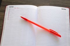 To Do List with Red Pen on Wooden Background. Closeup of to do list on wooden desk with red text numbered and red pen on notes pages with room for your own text Royalty Free Stock Image