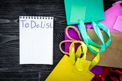 To do list for shopping among colorful paper bags on grey wooden background top view Stock Photography