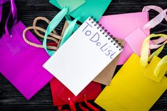 To do list for shopping among colorful paper bags on grey wooden background top view Stock Image