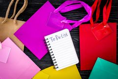 To do list for shopping among colorful paper bags on grey wooden background top view Royalty Free Stock Image