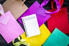 To do list for shopping among colorful paper bags on grey wooden background top view Royalty Free Stock Photos