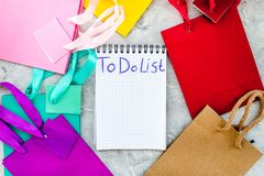 To do list for shopping at notebook near paper shopping bags on grey background top view mockup Royalty Free Stock Images