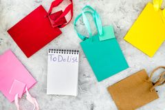 To do list for shopping at notebook among paper shopping bags on grey background top view Royalty Free Stock Photography