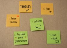 `to do list` Sticky Notes. On brown wall, such as call mom, yoga, finish laundry etc Stock Images