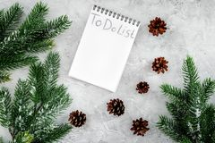 To do list for winter shopping at notebook near spruce branch and pinecones on grey stone background top view Royalty Free Stock Image
