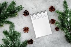 To do list for winter shopping at notebook near spruce branch and pinecones on grey stone background top view Royalty Free Stock Photo