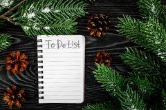 To do list for winter shopping at notebook near spruce branch and pinecones on grey wooden background top view Stock Photos