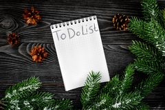 To do list for winter shopping at notebook near spruce branch and pinecones on grey wooden background top view Stock Photo