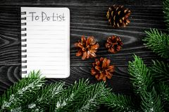 To do list for winter shopping at notebook near spruce branch and pinecones on grey wooden background top view Royalty Free Stock Images