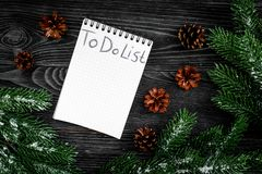 To do list for winter shopping at notebook near spruce branch and pinecones on grey wooden background top view Stock Images