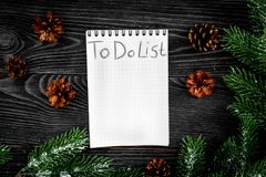To do list for winter shopping at notebook near spruce branch and pinecones on grey wooden background top view Royalty Free Stock Image