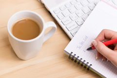 To do list. Woman writing a 'to do list' at her desk with a cup of fresh coffee Royalty Free Stock Image