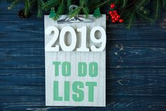 To do list on wooden pad, branches of fir tree, decor on grey wooden table. New Year Goals list, things to do on stock image