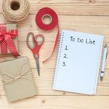 To Do List word with notebook, scissors and gift box decoration on wooden table, Top view and copy space. Happy New Year, Christma stock photos