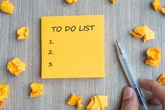 TO DO LIST word on yellow note with Businessman holding pen and crumbled paper on wooden table background. Business Goals, Mission royalty free stock images