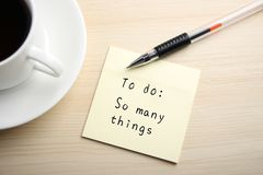 To do. A yellow sticky note is written something on the desk with a cup of coffee and a ball pen aside royalty free stock image
