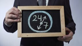 24 to 7 drawing on blackboard, businessman holding sign, business time concept. Stock footage stock video footage