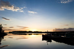 To Dream of Fish. Marina with Moored Boats on Glassy Water Reflecting Pattered Sky during Sunrise Royalty Free Stock Images