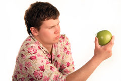 To eat or not eat, that's the question. A young man holds in his hand and looking at apple Royalty Free Stock Photography