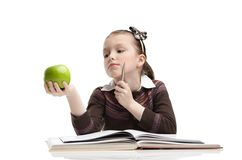 To eat or not to eat. Little girl hesitates about eating a ripe green apple, isolated, white background Royalty Free Stock Image