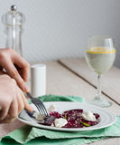 To eat a salad of  beets with goat cheese, oil and sesame, hands Stock Image