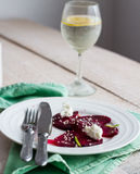 To eat a salad of  beets with goat cheese, oil and sesame, hands Royalty Free Stock Photography