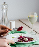 To eat a salad of  beets with goat cheese, oil and sesame, hands Stock Images